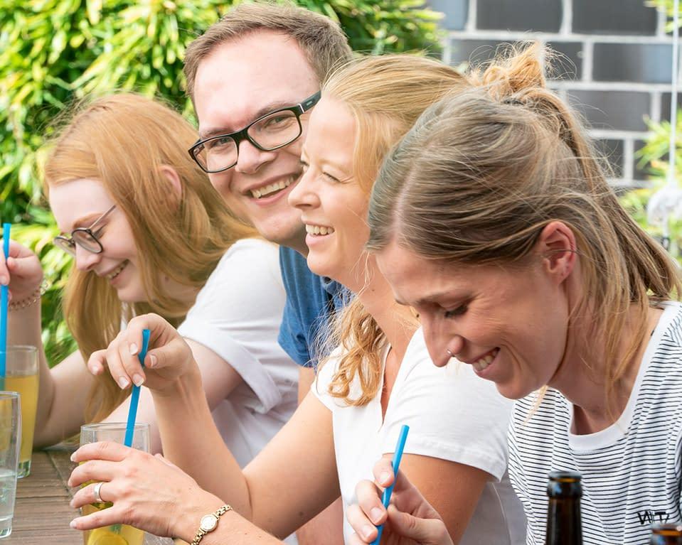 4 Mitarbeiter sitzen mit Getränken im Garten