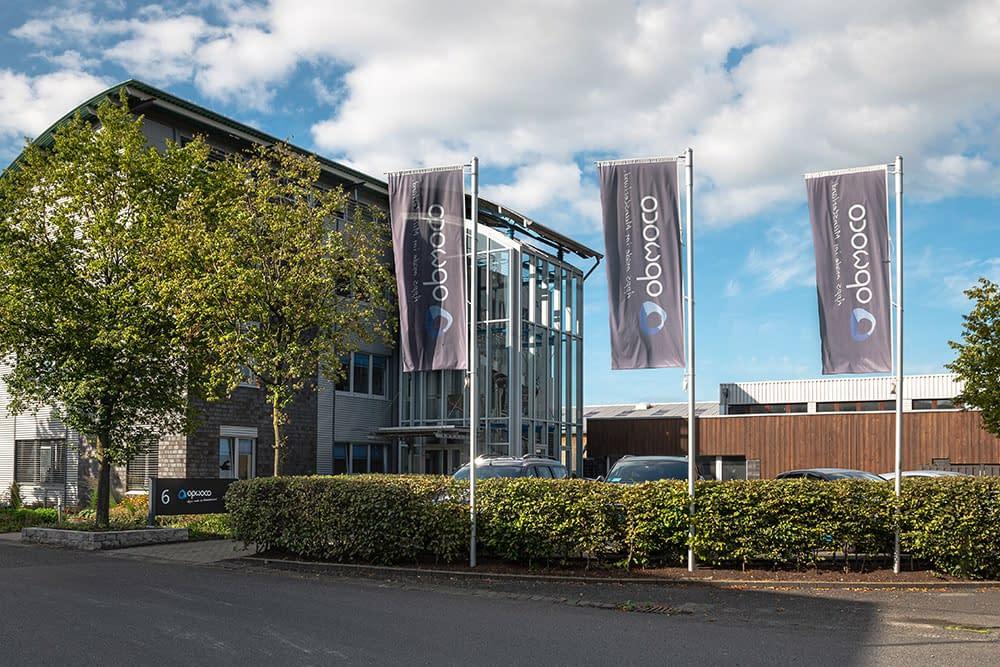 Das opwoco Firmengebäude. Ein mehrstöckiges Gebäude mit Parkplatz auf dem 3 Fahnenmaste mit opwoco flaggen hängen.