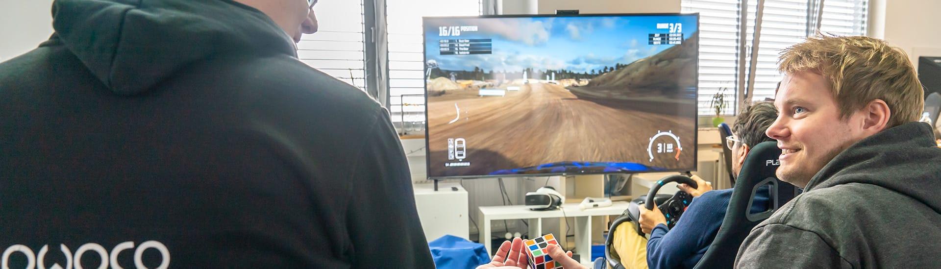 Mitarbeiter spielen ein Videospiel und mit einem Rubix Cube